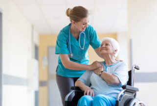 home health care worker pushing elderly lady in a wheelchair