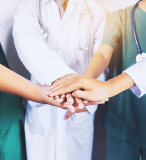 home health care workers putting hands on top of eachother in the center of a circle